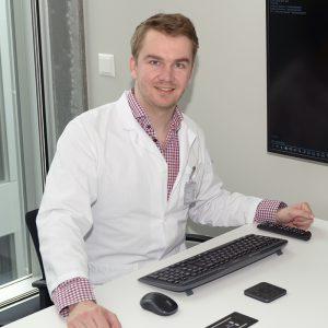 Das Bild zeigt den Gründer von derma2go und Oberarzt des Universitätsspitals Zürich Dr. med. Christian Greis am Schreibtisch sitzend.